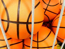 group of many new basketball orange balls with black lines at a sport shop ready to be sold behind some elastic white strings stock photo