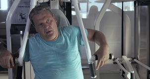 Close-up of grown man in gym performs exercises chest press. Close-up of grown man in gym sitting on the exerciser and performs exercises chest press and then stock video