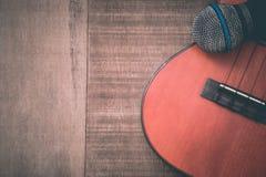 Close-up of grunge ukulele and microphone on wooden background Royalty Free Stock Photo