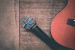 Close-up of grunge ukulele and microphone on wooden background Stock Image