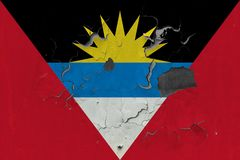 Close up grungy, damaged and weathered Antigua and Barbuda flag on wall peeling off paint to see inside surface.  royalty free stock image
