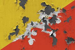 Close up grungy, damaged and weathered Bhutan flag on wall peeling off paint to see inside surface royalty free stock photography