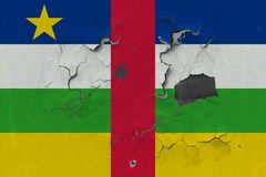 Close up grungy, damaged and weathered Central African Republic flag on wall peeling off paint to see inside surface.  stock photography