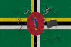 Close up grungy, damaged and weathered Dominica flag on wall peeling off paint to see inside surface.  royalty free stock photos
