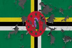 Close up grungy, damaged and weathered Dominica flag on wall peeling off paint to see inside surface.  stock images