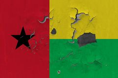 Close up grungy, damaged and weathered Guinea Bissau flag on wall peeling off paint to see inside surface.  royalty free stock photos