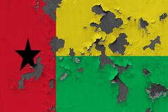 Close up grungy, damaged and weathered Guinea Bissau flag on wall peeling off paint to see inside surface.  stock photography