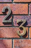 Close-up of grungy number 23 screwed onto distressed brick stock photography