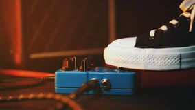 Close up of guitar player foot pressing pedal. Musician uses music effect loop machine. Man in trendy sneakers, his foot royalty free stock photography
