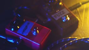Close up of guitar player or rock musician playing overdrive and fuzz pedal on his show. Man`s foot pressing on metal stock footage