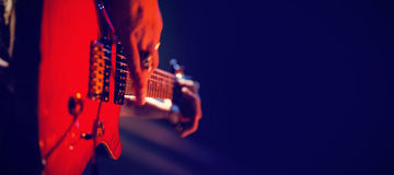Close-up of guitarist playing guitar on stage. Close-up of cropped guitarist playing guitar on stage in nightclub Stock Images