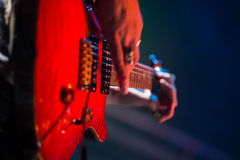 Close-up of guitarist playing guitar on stage. In nightclub Stock Photography