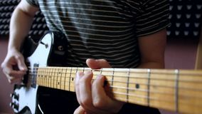 Musician plays on electro guitar in the studio.