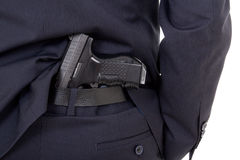 Close up of gun in business suit pants isolated on white. Background Stock Image