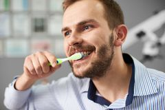 Close-up guy with beard cleans his teeth in dental office royalty free stock images