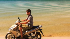 Close up Guy Drives Motorbike após a palma ao longo da praia aos barcos filme