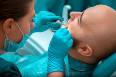 Close up of guy on the examination, the dentist checks the teeth Royalty Free Stock Images