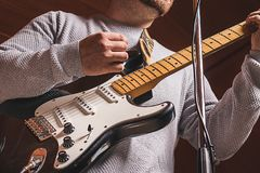 Close-up of a guy playing the electric guitar stock images