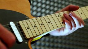 Close-up Guy Plays Guitar Touches Neck in Studio stock footage