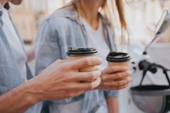 Close up of guy`s and girl`s hands holding cups of coffee. This poeple are sitting on motorcylcle and having some rest. Royalty Free Stock Images