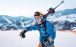 Close-up skier holding sticks on his shoulder of ski resort. Close-up a guy skier in a blue jacket, a yellow helmet and glasses is holding sticks on his shoulder Stock Photos