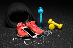 A close-up of gym accessories for sport training. Dumb-bells, bottle, and sport shoes with a smart phone on a floor. A close-up picture of black streching mat Royalty Free Stock Image