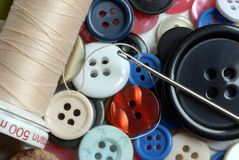 Spool of thread, sewing needle and plastic buttons stock image