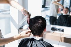Close up of a haircut at the hair saloon. Barber triming a client`s hair with a scissors. stock photography