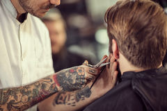 Close up hairdresser with scissors cut the beard Stock Photos