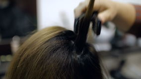 Close up of a hairdresser straightening long hair with hair irons. HD stock video