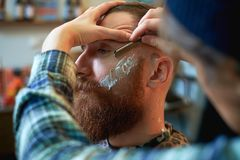 Close up of a hairdresses work for an attractive young blond man at the barber shop. He is doing styling of his beard. Close up of a hairdressers work for an Royalty Free Stock Images