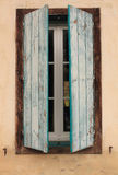 Close up of half opened rustic blue old window shutters on a beige facade of old farm house. View on half opened rustic blue old window shutters on a beige Royalty Free Stock Photos