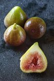 Close up of half sliced and three whole figs on a black reflective background with waterdrops. Shallow depth of field, focus on th Stock Photography