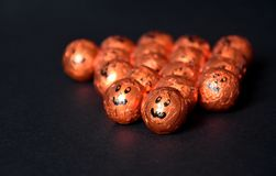 Close up of Halloween Jack-o-lantern foil covered sweets. Orange pumpkin wrapped chocolates in a row, on a black background. Close up of Halloween Jack-o-lantern Stock Images