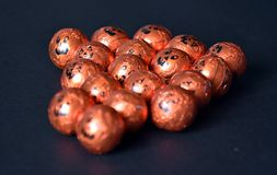 Close up of Halloween Jack-o-lantern foil covered sweets. Orange pumpkin wrapped chocolates in a row, on a black background. Close up of Halloween Jack-o-lantern Stock Image