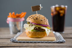 Close up of hamburger with french fries and drink in background Stock Photos