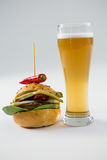 Close up of hamburger with jalapeno by beer glass Stock Photography