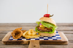 Close up of hamburger with onion rings and french fries Royalty Free Stock Images