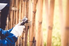 Close up hammer in hand rope fixing working construct fence. Retro and vintage style.nature environment idea design background.  stock photos