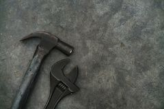 Close up hammer and monkey wrench. On grunge cement background stock photo