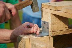 Close up of hammering a nail into wooden board royalty free stock photography
