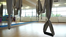 Close-up hammocks for fly yoga at the gym, slidecam. Close-up hammocks for yoga fly in a light gym, slidecam stock video