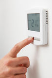 Close Up Of hand Adjusting Digital Central Heating Thermostat. Hand Adjusting Digital Central Heating Thermostat Co Stock Photos