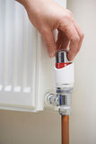 Close Up Of Hand Adjusting Heating Thermostat. At Home Royalty Free Stock Photos