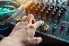 Close-up hand adjusting mixer sound on audio panel. Close-up hand adjusting mixer sound on control audio panel royalty free stock images