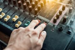 Close-up hand adjusting mixer sound on audio panel. Close-up hand adjusting mixer sound on control audio panel stock image