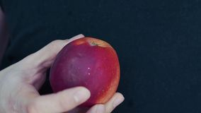 Close-up of the hand, the Apple in his hands twists on a black background stock video footage