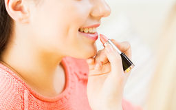 Close up of hand applying lipstick to woman lips Royalty Free Stock Photography