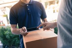 Close up of hand asian man using smartphone pressing screen to sign for delivery from the courier at home. Close up of hand asian men using smartphone pressing stock photos