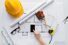 Close up of hand with blueprint and smartphone. Business, architecture, building, construction and people concept - close up of architect hand with living house royalty free stock photos